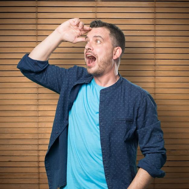 Junger mann mit einem blauen outfit tragen. schauen überrascht. Kostenlose Fotos