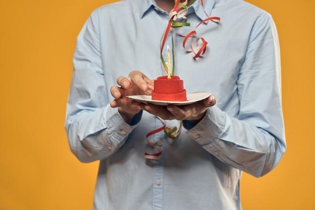 Junger mann mit einem festlichen kuchen mit scheiben feiert einen geburtstag in einer kappe, isolation und quarantäne Premium Fotos