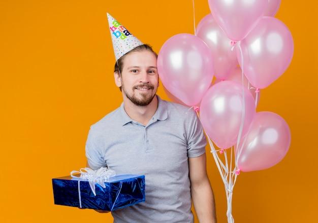 Junger mann mit feiertagsmütze, die geburtstagsfeier feiert, die bündel luftballons und geburtstagsgeschenk glücklich und fröhlich über orange hält Kostenlose Fotos