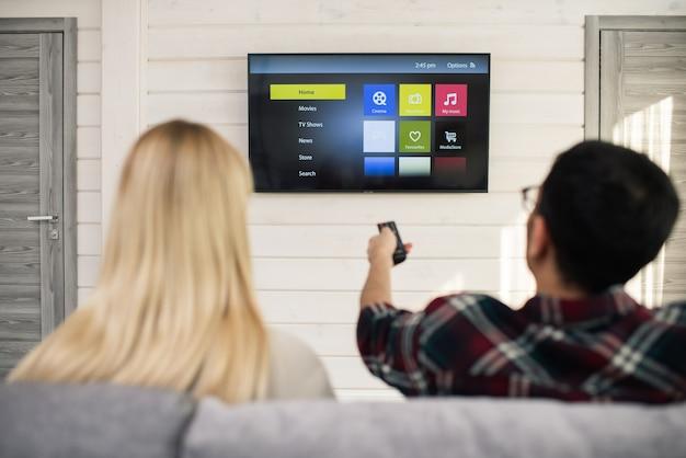 Junger mann mit fernbedienung, der etwas auswählt, um zu sehen, während er mit seiner freundin in der nähe vor dem fernseher sitzt Premium Fotos