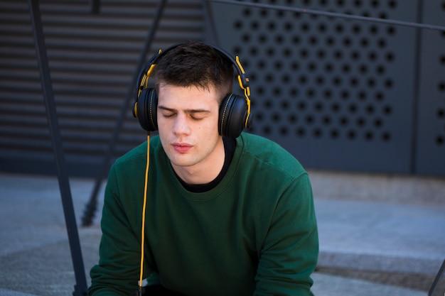 Junger mann mit geschlossenen augen hörend musik in den kopfhörern Kostenlose Fotos