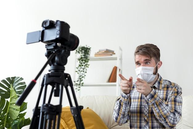 Junger mann mit gesichtsmaskenaufzeichnungsvideo zu hause Kostenlose Fotos