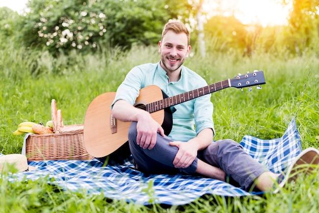 Junger mann mit gitarre auf picknick Kostenlose Fotos