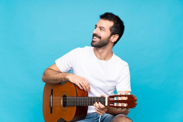 Junger mann mit gitarre über der lokalisierten blauen wand glücklich und dem lächeln Premium Fotos
