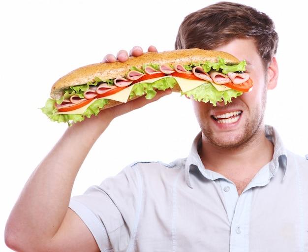 Junger mann mit großem sandwich Kostenlose Fotos