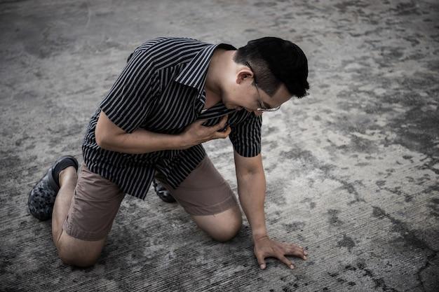 Junger mann mit herzinfarkt draußen, brauchen sie hilfe. Premium Fotos