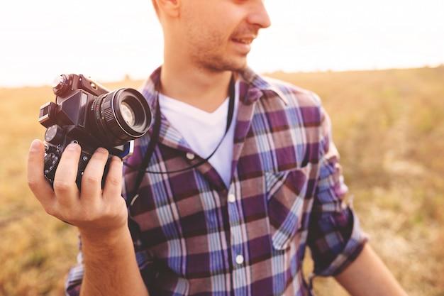Junger mann mit hippie-lebensstil der retro- fotokamera im freien Kostenlose Fotos
