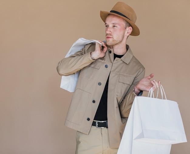Junger mann mit hut auf kopf und einkaufsnetzen Kostenlose Fotos