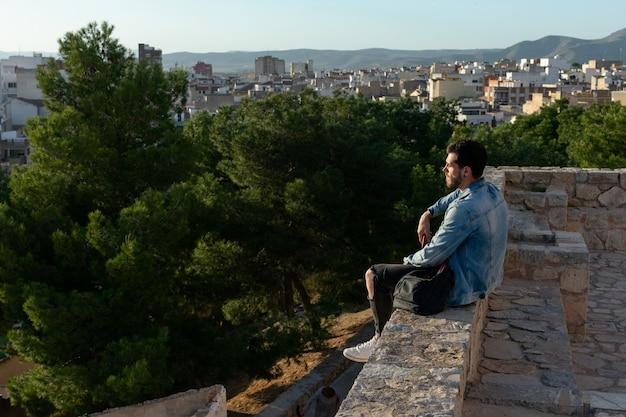 Junger mann mit kappe und jacke schaut die stadt. lifestyle-konzept, modell. Premium Fotos