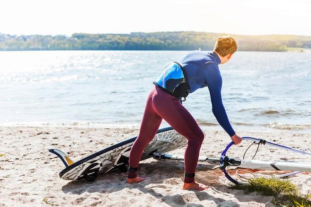 Junger mann mit kitesurfbrett Kostenlose Fotos