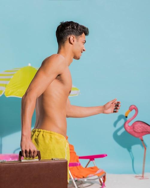 Junger mann mit koffer am strand spazieren Kostenlose Fotos
