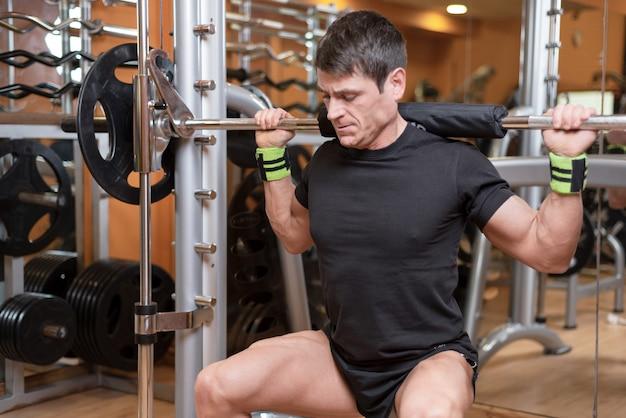 Junger mann mit langhantel kniebeugen im fitnessstudio zu tun. Premium Fotos