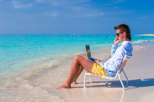 Junger mann mit laptop und handy am tropischen strand Premium Fotos