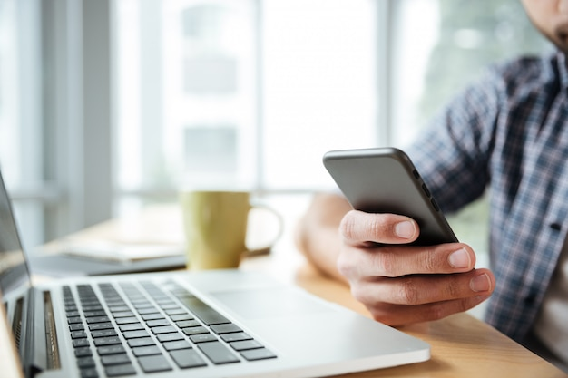 Junger mann mit laptop und telefon. Kostenlose Fotos