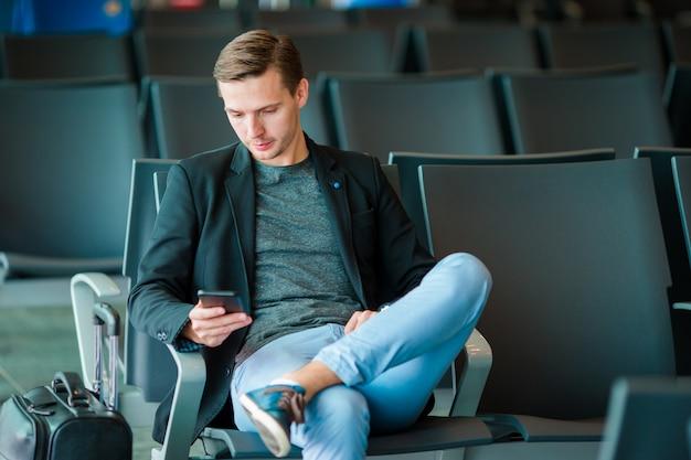 Junger mann mit mobiltelefon am flughafen beim warten auf einstieg. Premium Fotos