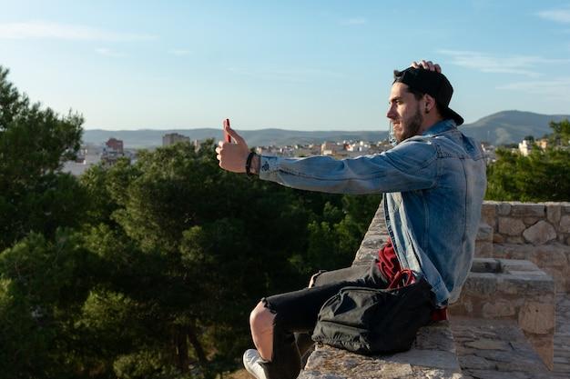 Junger mann mit mütze macht ein foto mit der stadt im hintergrund. Premium Fotos
