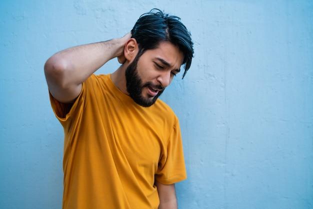 Junger mann mit nackenschmerzen. Kostenlose Fotos