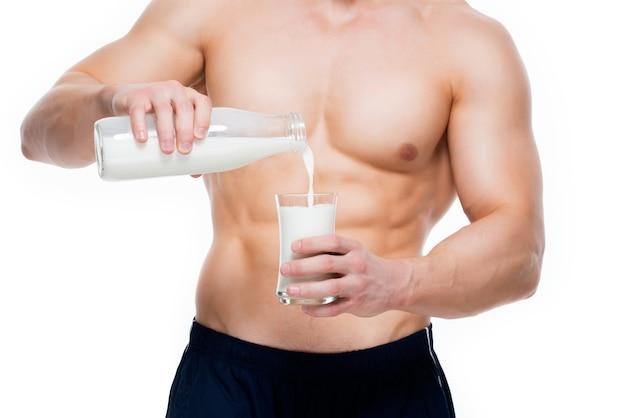 Junger mann mit perfektem körper, der milch in ein glas gießt - lokalisiert auf weißer wand. Kostenlose Fotos