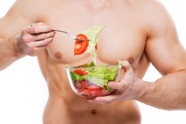 Junger mann mit perfektem körper hält salat - lokalisiert auf weißer wand. Kostenlose Fotos