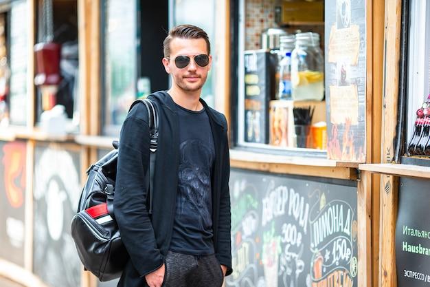 Junger mann mit rucksack auf straßenlebensmittelmarkt draußen Premium Fotos