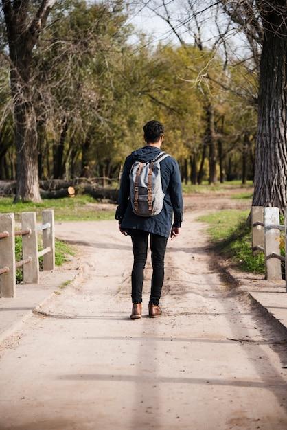 Junger mann mit rucksack im park spazieren Kostenlose Fotos
