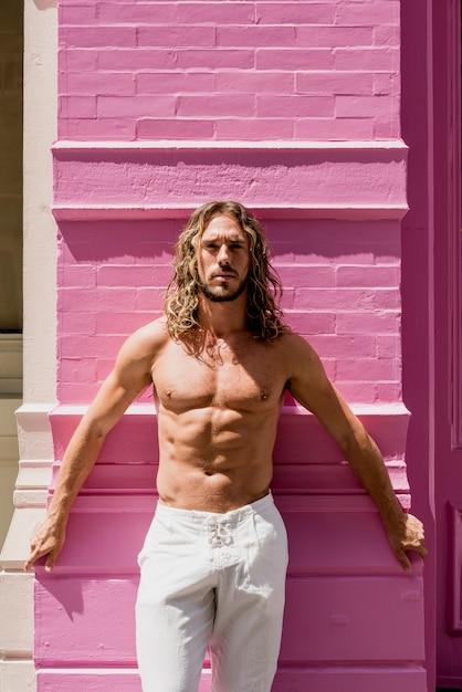 Junger mann mit sechs sätzen, der auf rosa wand aufwirft Kostenlose Fotos