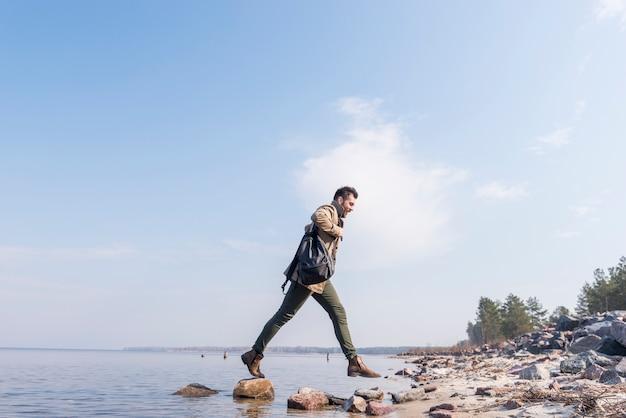Junger mann mit seinem rucksack auf der schulter, die über die steine nahe dem see springt Kostenlose Fotos