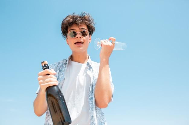 Junger mann mit sonnenbrille und champagnerflasche Kostenlose Fotos