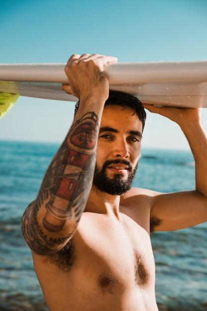 Junger mann mit surfbrett am kopf am strand in der nähe von wasser Kostenlose Fotos