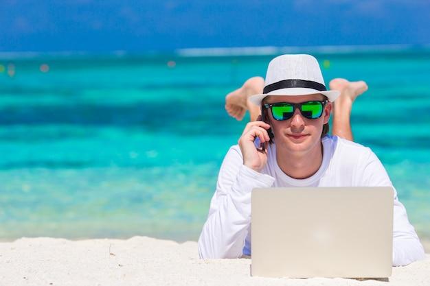 Junger mann mit tablet-computer und handy am tropischen strand Premium Fotos