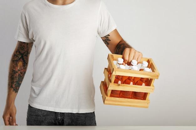 Junger mann mit tätowierungen in jeans und einem einfachen weißen t-shirt hält eine holzkiste mit sechs unbeschrifteten flaschen alkoholfreier getränke Kostenlose Fotos