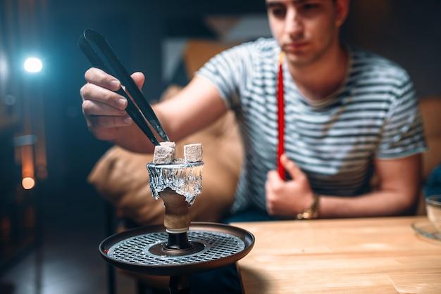 Junger mann mit zange entzündet die kohle an der shisha-bar Premium Fotos