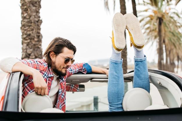 Junger mann nahe den beinen der frau, die sich heraus vom auto lehnen Kostenlose Fotos