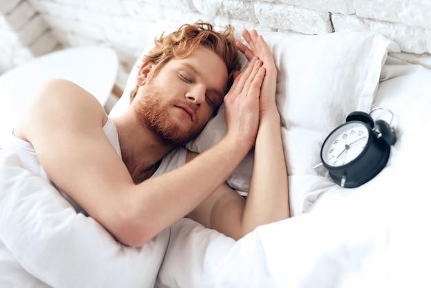 Junger mann schläft unter weißer decke. süße träume. Premium Fotos