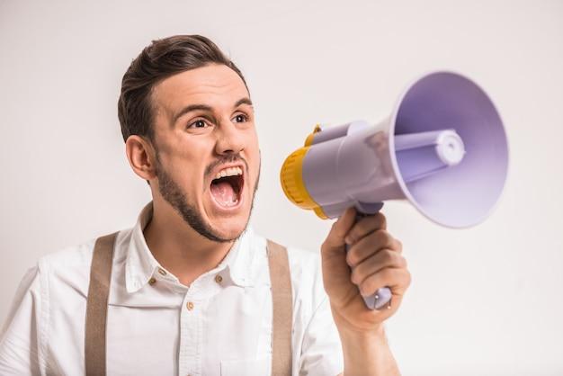 Junger mann schreit in einem megaphon vorbei. Premium Fotos