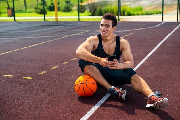 Junger mann sitzt auf dem basketballplatz Kostenlose Fotos