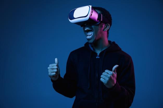 Junger mann spielt in vr-brille im neonlicht auf gradient Kostenlose Fotos