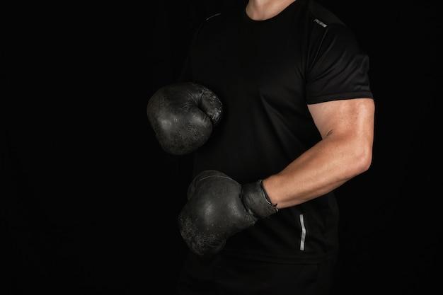 Junger mann steht in einem boxgestell und trägt sehr alte schwarze boxhandschuhe der weinlese Premium Fotos