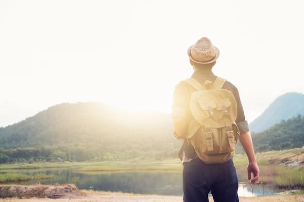 Junger mann traveller mit rucksack entspannenden outdoor. Kostenlose Fotos