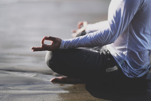 Junger mann üben yoga am strand bei sonnenuntergang. Premium Fotos