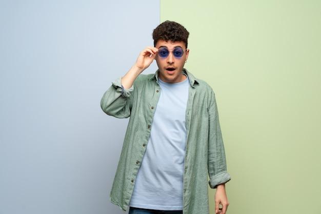 Junger mann über blau und grün mit brille und überrascht Premium Fotos