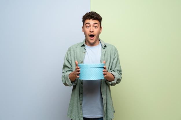 Junger mann über blauer und grüner wand überrascht, weil ein geschenk gegeben worden ist Premium Fotos
