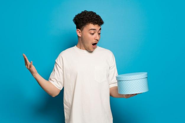 Junger mann über dem blauen hintergrund, der geschenkbox in den händen hält Premium Fotos