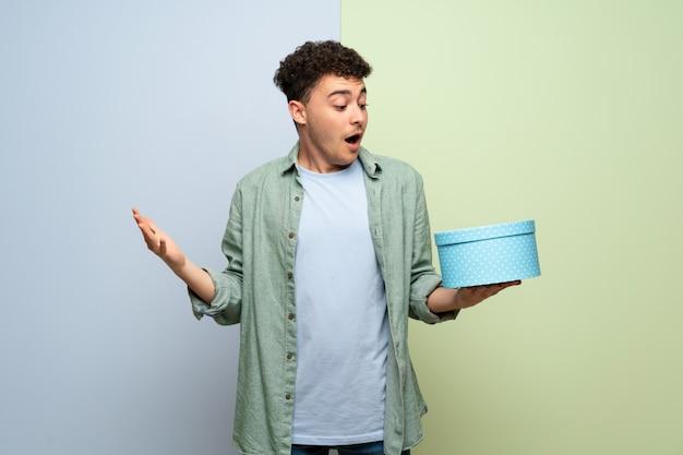 Junger mann über der blauen und grünen wand, die geschenkbox in den händen hält Premium Fotos