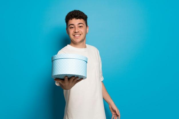 Junger mann über der blauen wand, die ein geschenk in den händen hält Premium Fotos