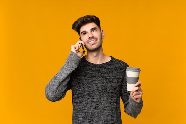 Junger mann über der lokalisierten wand, die kaffee hält, um und ein mobile wegzunehmen Premium Fotos