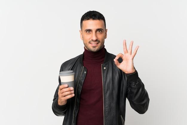 Junger mann über der lokalisierten weißen wand, die kaffee hält, um bei der herstellung des okayzeichens wegzunehmen Premium Fotos