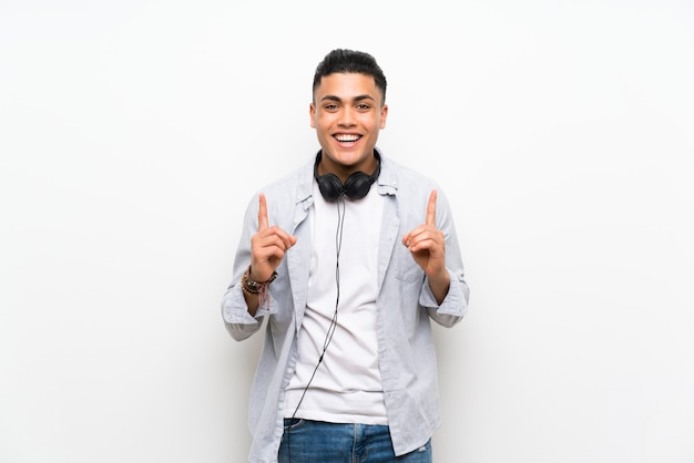 Junger mann über lokalisierter weißer wand mit kopfhörern eine großartige idee oben zeigend Premium Fotos