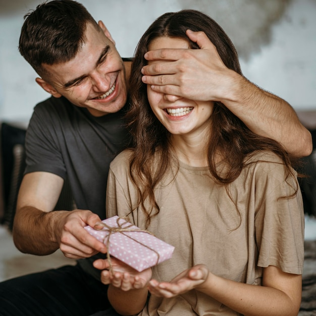 Junger mann überraschende freundin mit geschenk Kostenlose Fotos