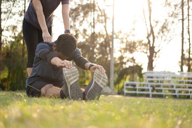 Junger mann und frau, die im park strecken. Premium Fotos